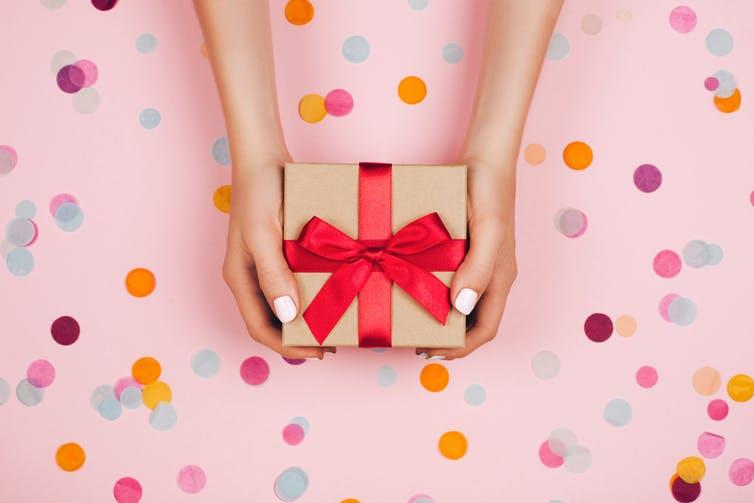Gift wrap hands with wall. Efetova Anna/Shutterstock.com